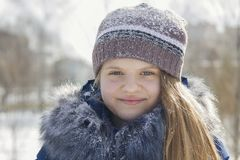 Retrato de la muchacha adolescente en casquillo y chaqueta con el cuello de la piel en el invierno cubierto por la nieve Fotos de archivo