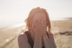 Retrato de la muchacha adolescente feliz en la playa que la cierra Imagen de archivo