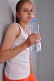 Retrato de la muchacha adolescente juguetona joven con una botella de agua potable Imagenes de archivo
