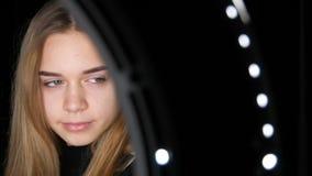 Retrato de la muchacha adolescente linda con las actitudes del pelo blanco largo y de los ojos verdes para la c?mara en estudio P almacen de video