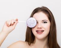 Retrato de la muchacha adolescente que muestra apoyos dentales y que sostiene el caramelo Fotos de archivo