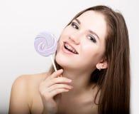 Retrato de la muchacha adolescente que muestra apoyos dentales y que sostiene el caramelo Fotografía de archivo