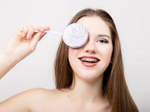 Retrato de la muchacha adolescente que muestra apoyos dentales y que sostiene el caramelo Imagenes de archivo