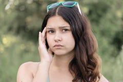 Retrato de la muchacha adolescente que piensa en un problema en la naturaleza Foto de archivo