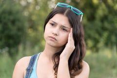 Retrato de la muchacha adolescente que piensa en un problema en la naturaleza Foto de archivo libre de regalías