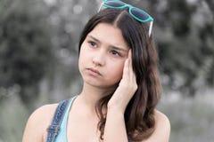 Retrato de la muchacha adolescente que piensa en un problema en la naturaleza Fotografía de archivo libre de regalías
