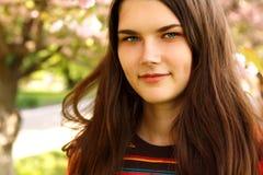 Retrato de la muchacha adolescente que sonríe sobre cereza del japonés del jardín de la naturaleza Imagen de archivo