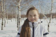 Retrato de la muchacha adolescente regordeta entre los árboles en invierno Imagen de archivo