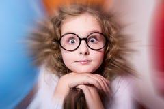 Retrato de la muchacha adolescente rizada sorprendida en vidrios en el backgrou Imagen de archivo