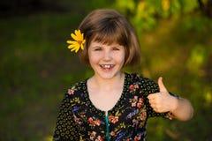 Retrato de la muchacha adorable con la flor en pelos, mostrando los pulgares para arriba fotografía de archivo libre de regalías