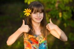 Retrato de la muchacha adorable con la flor, mostrando los pulgares para arriba imagen de archivo libre de regalías