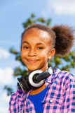 Retrato de la muchacha africana feliz con los auriculares Imagen de archivo libre de regalías