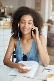 Retrato de la muchacha africana hermosa feliz que escucha la música en sentarse sonriente de los auriculares en café Ojos cerrado Imagen de archivo libre de regalías