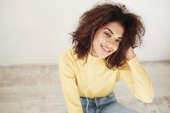 Retrato de la muchacha africana hermosa joven en auriculares que sonríe mirando la cámara que se sienta en piso Fotografía de archivo
