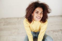 Retrato de la muchacha africana hermosa joven en el guiño sonriente de los auriculares mirando la cámara que se sienta en piso Foto de archivo