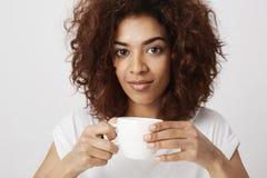 Retrato de la muchacha africana hermosa que sonríe sosteniendo la taza de café que mira la cámara Foto de archivo libre de regalías