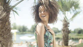 Retrato de la muchacha afroamericana adolescente hermosa en la playa tropical que presenta a una cámara Fotografía de archivo