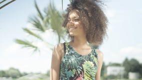Retrato de la muchacha afroamericana adolescente hermosa en la playa tropical que presenta a una cámara Fotografía de archivo libre de regalías