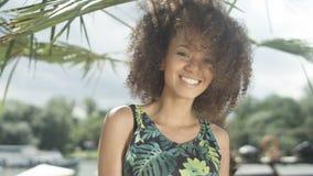 Retrato de la muchacha afroamericana adolescente hermosa en la playa tropical que sonríe a una cámara Imagen de archivo libre de regalías