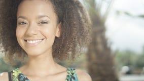 Retrato de la muchacha afroamericana adolescente hermosa en la playa tropical que sonríe a una cámara Foto de archivo libre de regalías