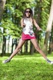Retrato de la muchacha afroamericana feliz y activa del adolescente que hace un salto de altura Imágenes de archivo libres de regalías