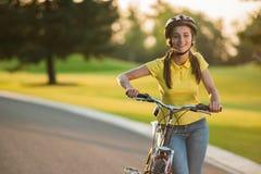 Retrato de la muchacha alegre con la bicicleta al aire libre Fotografía de archivo libre de regalías