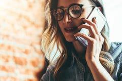 Retrato de la muchacha alegre del blogger en los vidrios que se sientan en café, hablando en el teléfono El empresario tiene conv foto de archivo libre de regalías