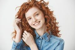 Retrato de la muchacha alegre del jengibre que sonríe mirando la cámara sobre el fondo blanco Foto de archivo libre de regalías