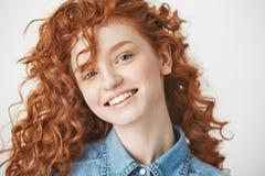 Retrato de la muchacha alegre del jengibre que sonríe mirando la cámara sobre el fondo blanco Fotos de archivo libres de regalías