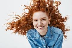 Retrato de la muchacha alegre hermosa del pelirrojo con volar la risa sonriente del pelo rizado mirando la cámara sobre blanco Imágenes de archivo libres de regalías