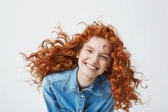 Retrato de la muchacha alegre hermosa del pelirrojo con volar la risa sonriente del pelo rizado mirando la cámara sobre blanco Fotos de archivo