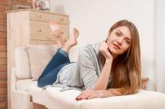 Retrato de la muchacha alegre que miente en el sofá y la sonrisa Imagenes de archivo