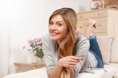 Retrato de la muchacha alegre que miente en el sofá y la sonrisa Fotografía de archivo