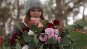 Retrato de la muchacha asiática caucasial de la raza mixta hermosa que sostiene un ramo de flores en bosque nevoso del pino del i metrajes
