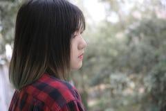 Retrato de la muchacha asiática con la mirada en alguna parte encendido del backg de la naturaleza Imagen de archivo
