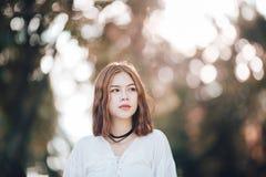 Retrato de la muchacha asiática del inconformista joven que presenta en el fondo del bokeh del bosque del parque del otoño Foto de archivo libre de regalías
