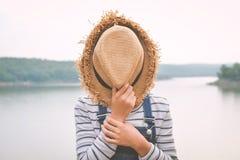 Retrato de la muchacha asiática feliz que sostiene el sombrero en naturaleza Fotos de archivo