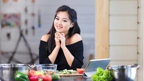 Retrato de la muchacha asiática joven adorable que sonríe y que presenta mirando la cámara en cocina almacen de metraje de vídeo