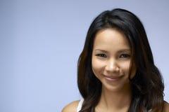 Retrato de la muchacha asiática que mira la cámara y la sonrisa Imagen de archivo