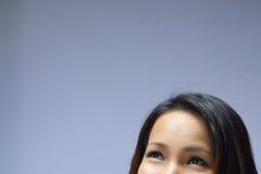 Retrato de la muchacha asiática que mira para arriba y que sonríe Fotografía de archivo