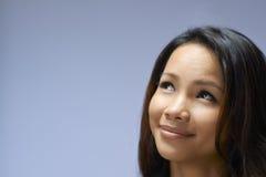 Retrato de la muchacha asiática que mira para arriba y que sonríe Imagenes de archivo