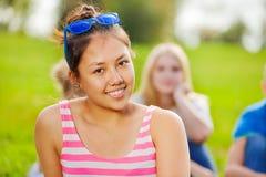 Retrato de la muchacha asiática que se sienta en hierba en parque Fotos de archivo