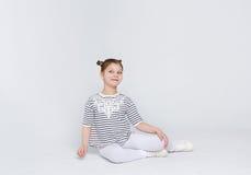 Retrato de la muchacha asombrosa divertida que se sienta en el piso en el fondo blanco Imagen de archivo