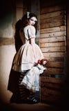 Retrato de la muchacha asustadiza extraña con la muñeca a disposición Fotografía de archivo libre de regalías