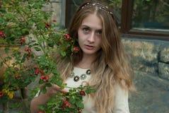 Retrato de la muchacha atractiva cerca del dogrose Fotografía de archivo