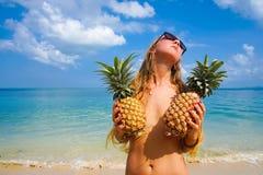 Retrato de la muchacha atractiva con las piñas con el mar tropical en el fondo Estilo del partido de la playa Foto de archivo libre de regalías