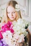 Retrato de la muchacha atractiva con un ramo de flores Foto de archivo libre de regalías