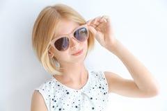 Retrato de la muchacha atractiva del adolescente en gafas de sol, aislado en blanco Foto de archivo