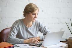 Retrato de la muchacha atractiva del estudiante en el escritorio con el ordenador portátil Fotografía de archivo libre de regalías