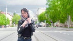 Retrato de la muchacha atractiva en chaqueta de cuero negra en el fondo de la ciudad Manos que sostienen la bufanda gris vestida  metrajes